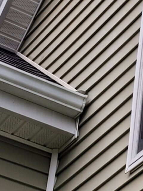 We use rain diverters to prevent water from getting between wall and end of gutter. -